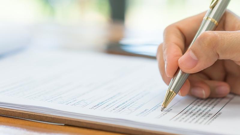 Hand som fyller i ett formulär