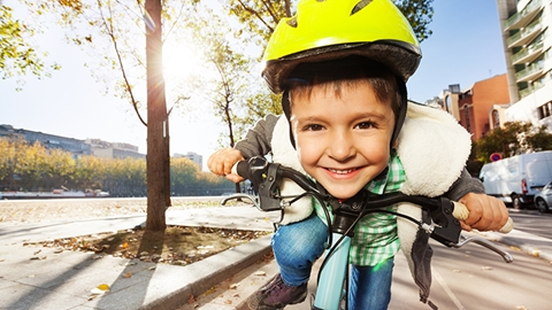Glad pojke med cykelhjälm